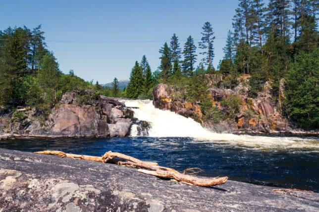 vodopád v Norsku s vyplaveným stromem v popředí