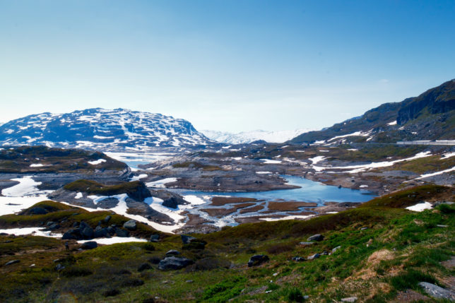 Norské hory s posledními zbytky sněhu a modrým jezerem