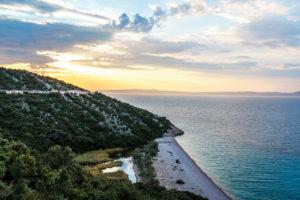 západ slunce za kopcem, po kterém vede cesta a pod kopcem jezero s nedostupnou pláží pouze z moře