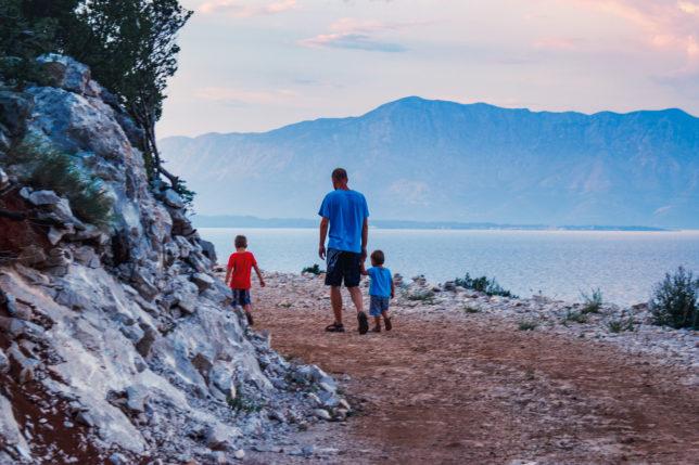 chorvatsko bez turistů, tatínek se prochází se dvěma syny při západu slunce