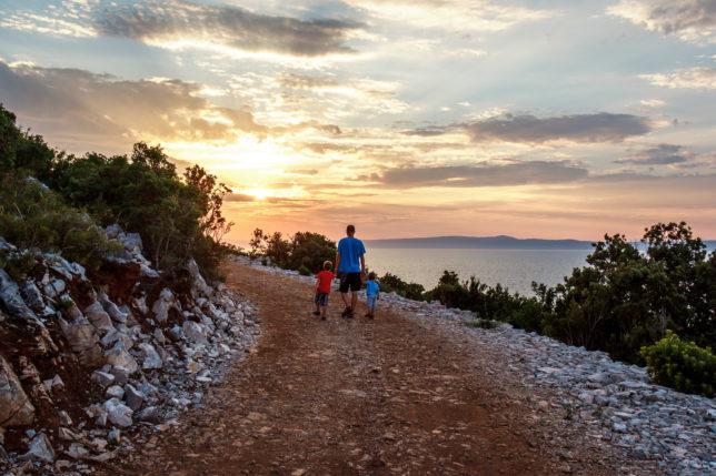tatínek se syny na procházce při západu slunce
